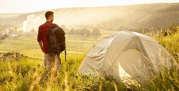 تصویر مرد جوان در کنار چادر در طبیعت