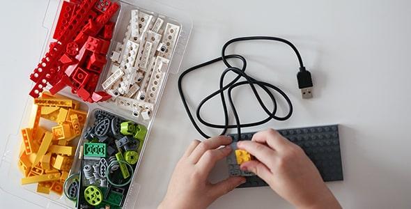 تصویر بچه در حال بازی با لگو و ساخت ربات